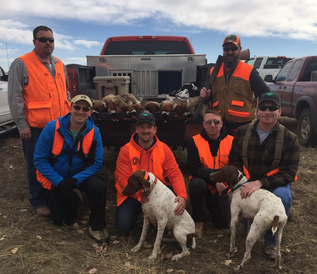 A group of men and dogs with their catch after a successful hunt at longmeadow
