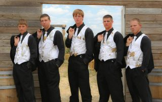 Groom and his grooms men standing with their jackets over their shoulders