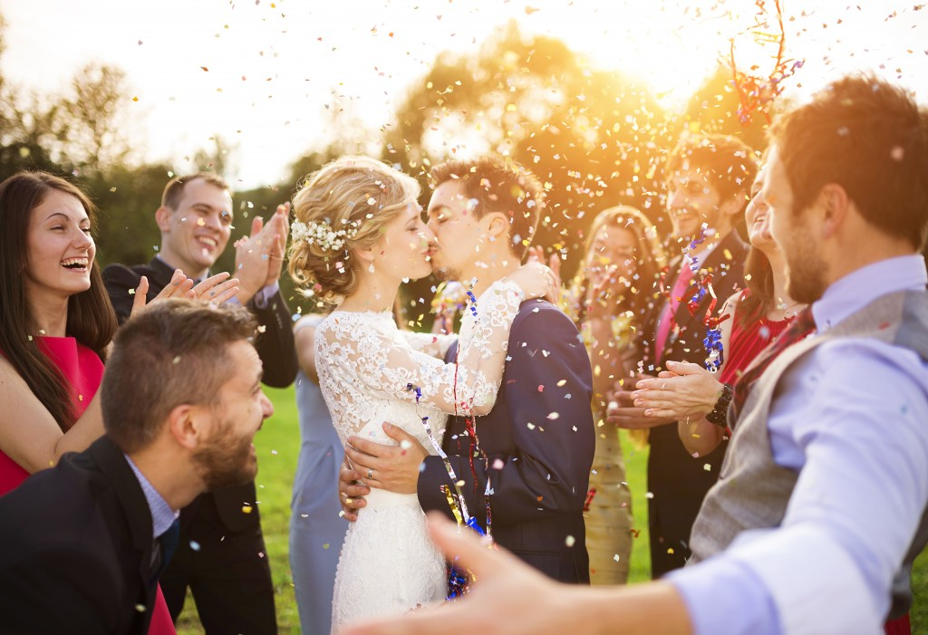 A picture of a groom kissing a bride while their friend happily throw rice into the air around them