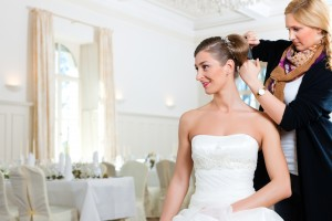 A picture of a wedding planner fixing a bride's hair