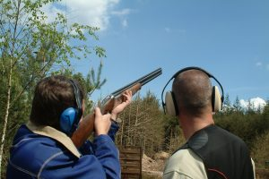 man shooting clay pigeons being instructed, sporting clays rates