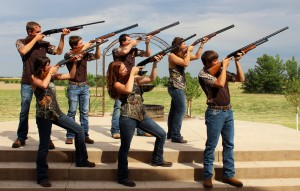 Several men and women holding shotguns pointed at the sky