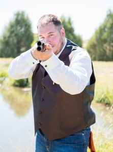A man holding a shotgun pointed at the camera