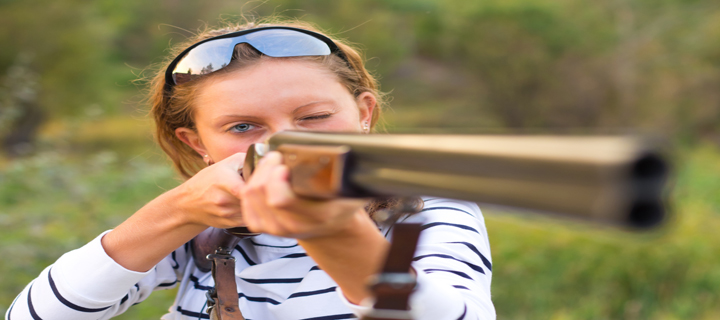 a young girl with a gun for shooting clays and shooting glasses aiming at a target