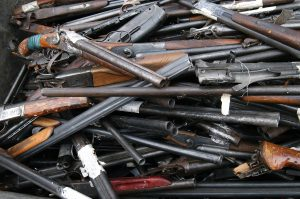 rubbish container with broken shotguns, rifles and other old weapons