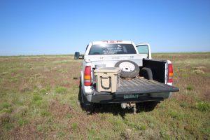 white truck with the word longmeadow in the back window sitting in a field