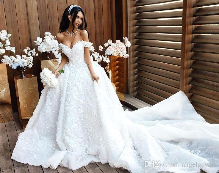 A blushing bride surrounded by white flowers - Sexiest Wedding Dresses 2019