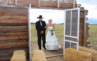 wedding photo of groom and bride in cow boy boots and cowboys hats
