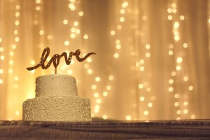 A picture of a wedding cake backlit by several strands of white lights