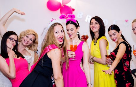 Cheerful bride and happy bridesmaids celebrating hen party with drinks. Women enjoying a bachelorette party dancing.